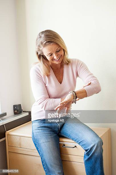 happy mature female teacher looking at watch while sitting on cabinet - watch timepiece stock pictures, royalty-free photos & images
