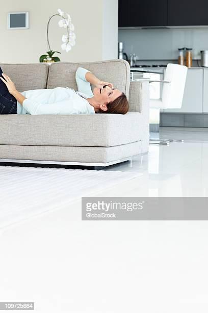 Maduro feliz mujer usando cellphone mientras están recostadas en el sofá