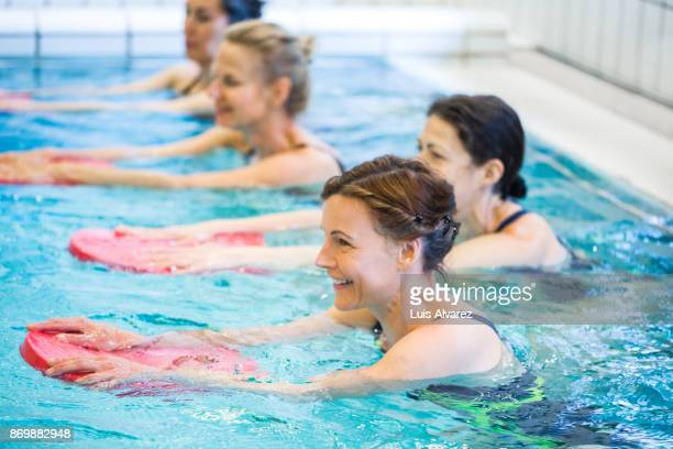 happy mature females exercising in swimming pool - hydrotherapy stock photos and pictures