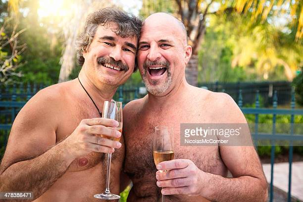 happy mature gay bear couple with drinks on florida holiday - naturist male stock pictures, royalty-free photos & images