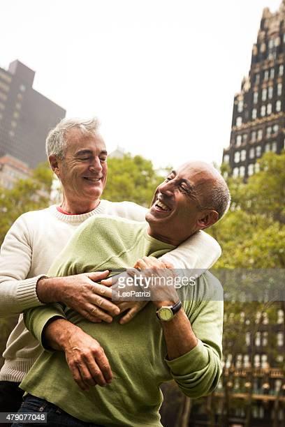 gay couple mature heureux s'amuser en plein air dans la ville - gay seniors photos et images de collection