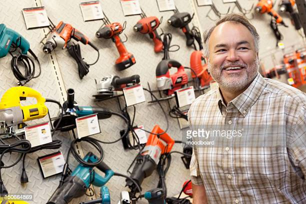 Happy mature hardware store owner looking away