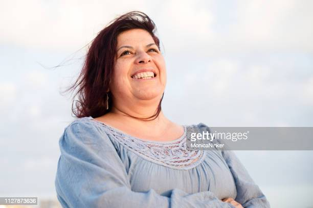 happy mature hispanic woman - fat woman at beach stock pictures, royalty-free photos & images