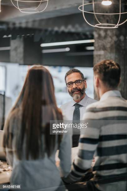 happy mature insurance agent talking to a couple in the office. - bank customer stock pictures, royalty-free photos & images