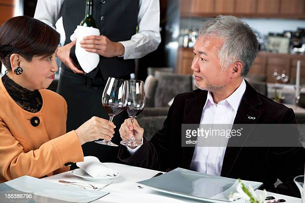 Happy mature Japaneese couple toasting in a restaurant