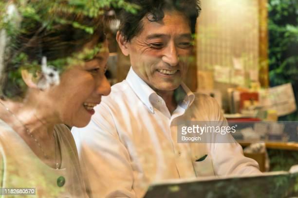 京都のレストランメニューを見る幸せな成熟した日本人カップル - ティールーム ストックフォトと画像