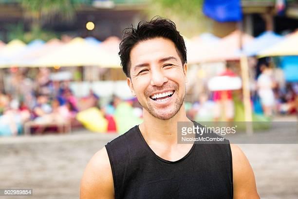 Happy mature Japanese man smiling at beach fair