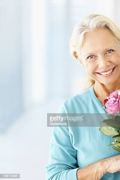 Happy mature lady holding a fresh flower with copy space