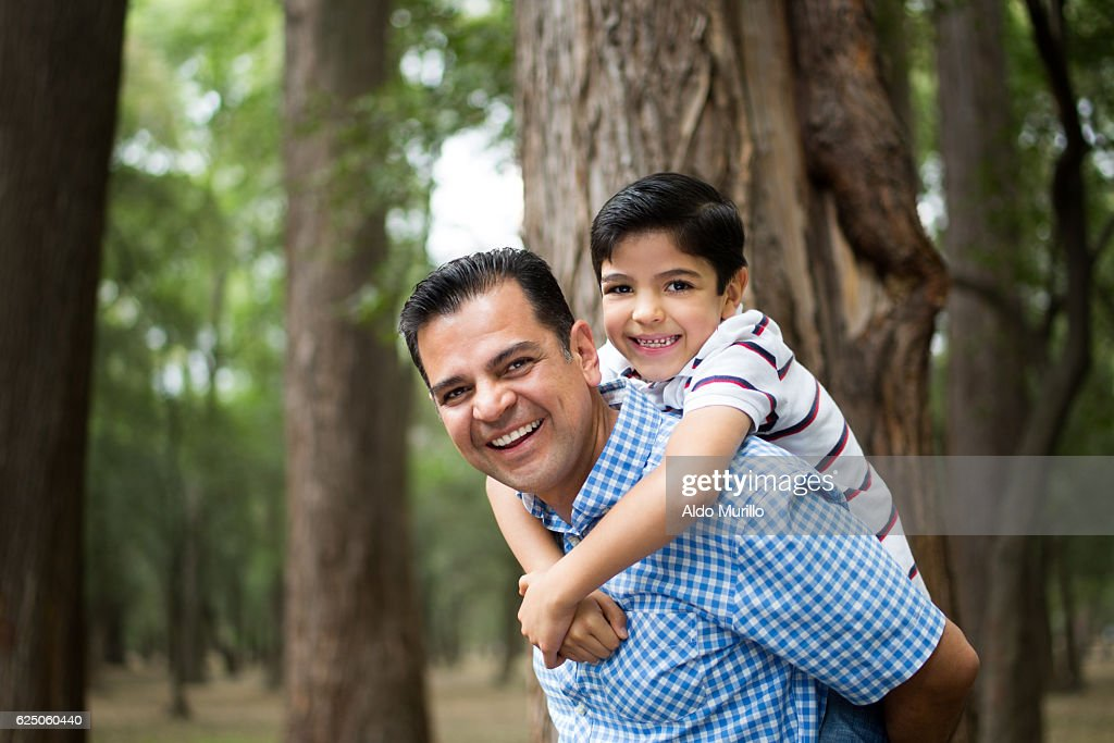 Happy mature latin father carrying son on back : Stock-Foto