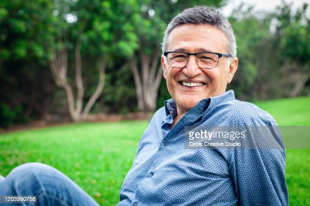 gelukkige rijpe mannelijke mens die glimlacht - 60 64 jaar stockfoto's en -beelden