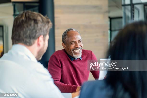 happy mature male manager sitting with colleagues - mature men stock pictures, royalty-free photos & images