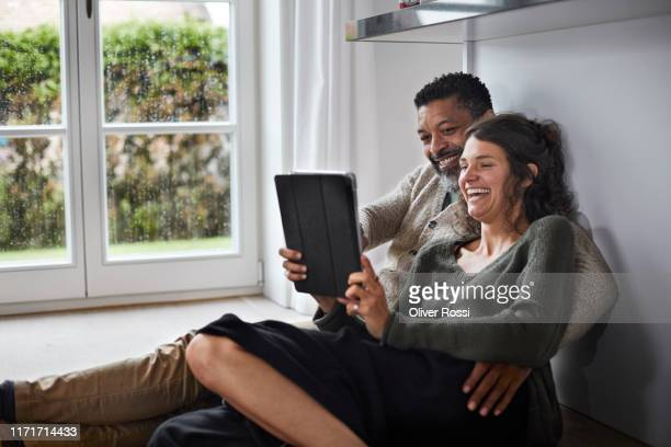 happy mature man and young woman sitting on the floor using tablet - seulement des adultes photos et images de collection