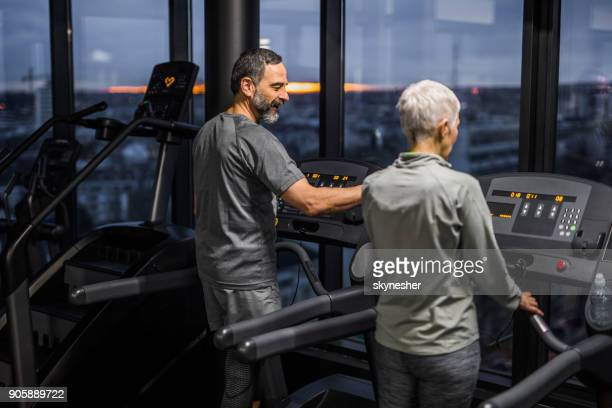 Happy mature man assisting woman during sports training on a treadmill.