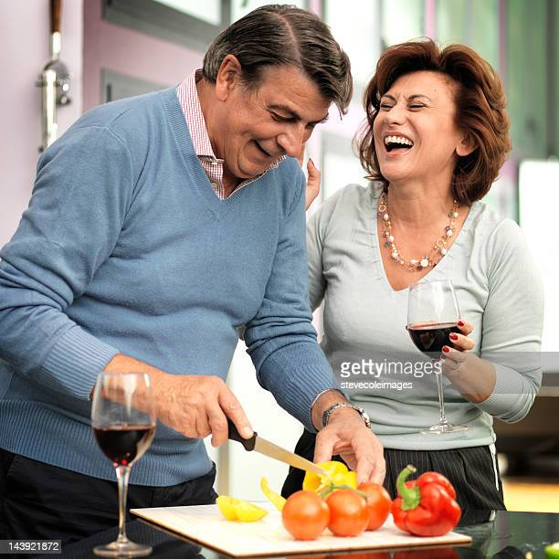Happy Mature Man Chopping Vegetable And Woman Holding Wine