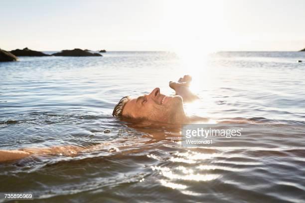 happy mature man floating in the sea - sorglos stock-fotos und bilder