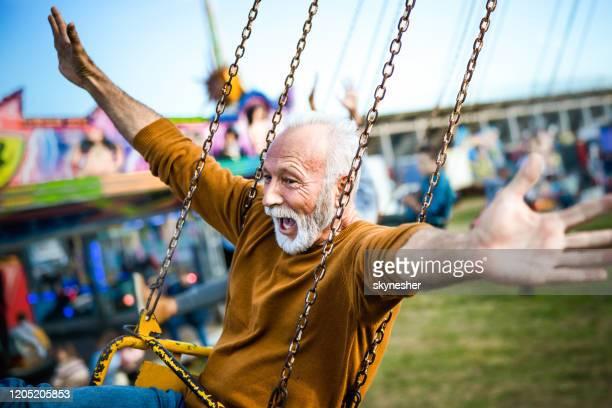 gelukkige rijpe mens die pret op een rit van de kettingschommeling bij pretpark heeft. - kunst cultuur en vermaak stockfoto's en -beelden