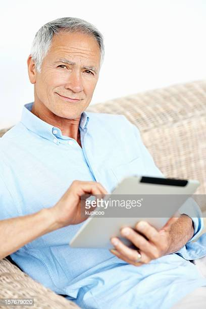 Happy mature man holding a tablet PC against white background