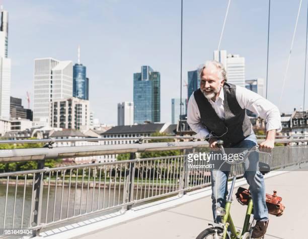 happy mature man on bicycle crossing bridge in the city - ヘッセン州 ストックフォトと画像