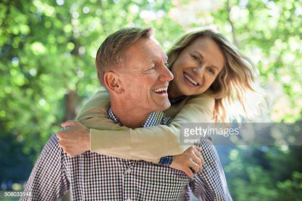 Happy mature man piggybacking his wife in a park