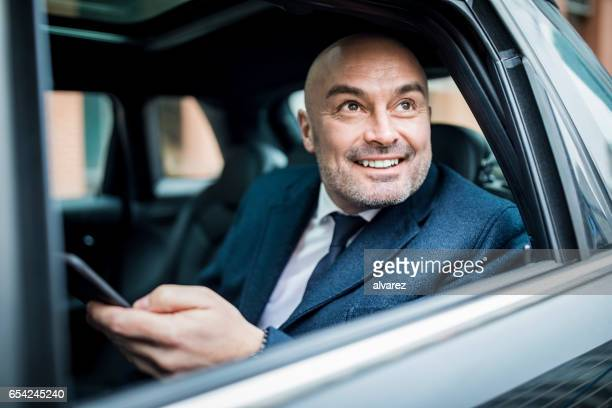 Happy mature man sitting in back seat of car
