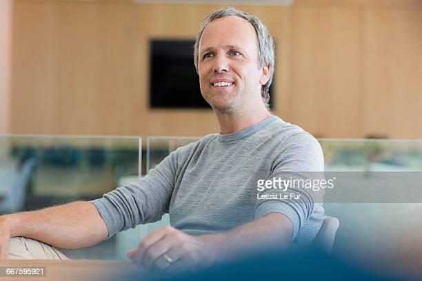 Happy mature man sitting in living room