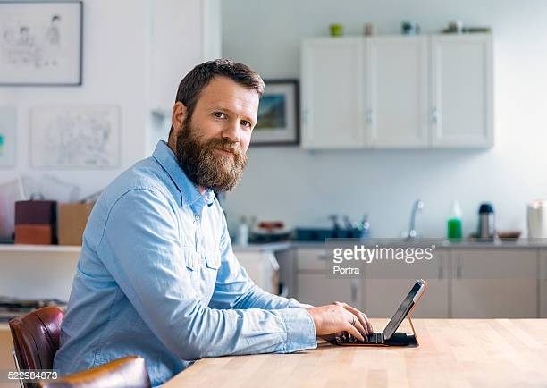 Happy mature man using laptop at table