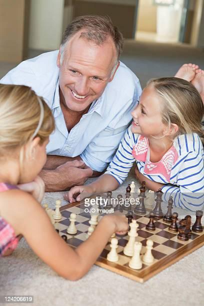Happy mature man watching kids play chess at home