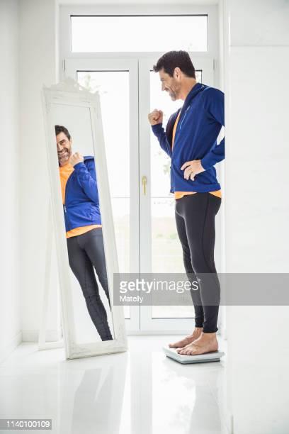happy mature man weighing himself whilst looking in mirror at home - trainingsanzug stock-fotos und bilder