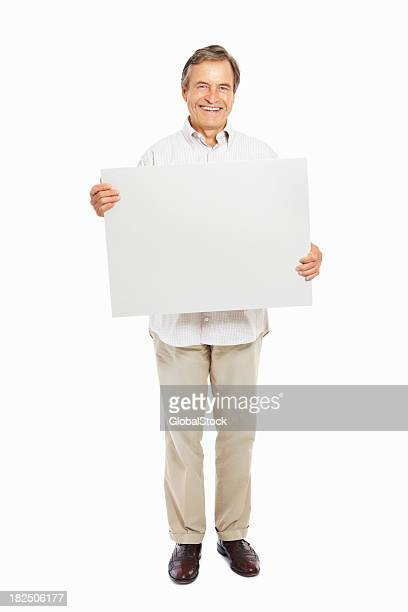 Happy mature man with a blank signboard isolated on white