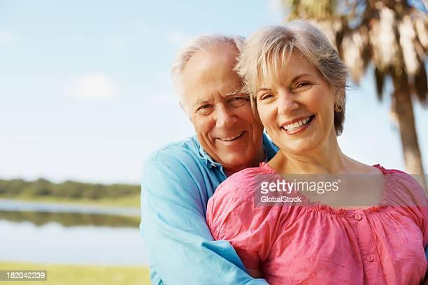 Glücklich Älterer Mann mit Armen seiner Frau
