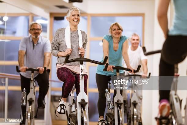 gerne ältere menschen bei der ausübung bikes während spinnen klasse in einem fitnessstudio. - anstoß sportbegriff stock-fotos und bilder