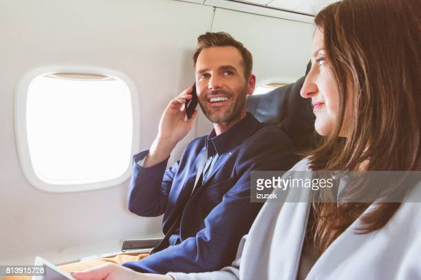 Happy mature people traveling by airplane