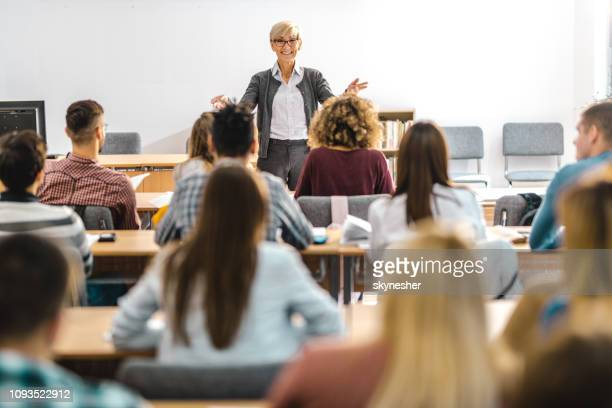 happy mature professor giving a lecture in front of her students at lecture hall. - classroom stock pictures, royalty-free photos & images