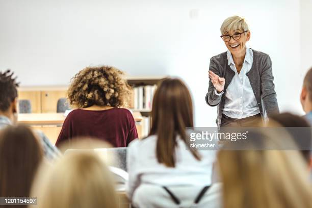 happy mature professor giving a lecture in front of her students at lecture hall. - professor stock pictures, royalty-free photos & images