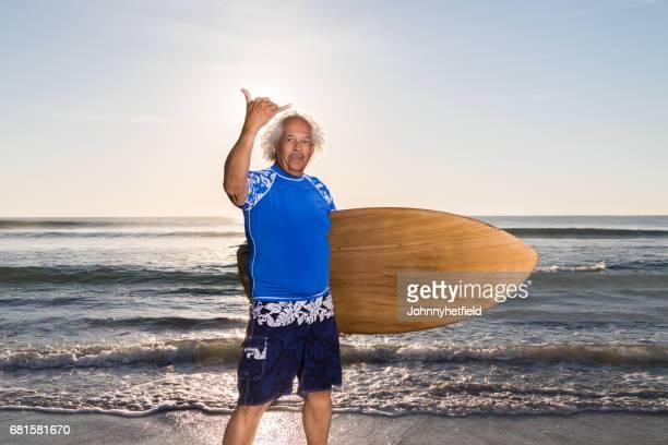 Happy mature surfer at sunrise