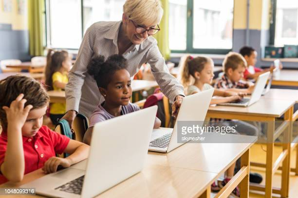 happy mature teacher assisting school kids in using computers on a class. - classroom stock pictures, royalty-free photos & images