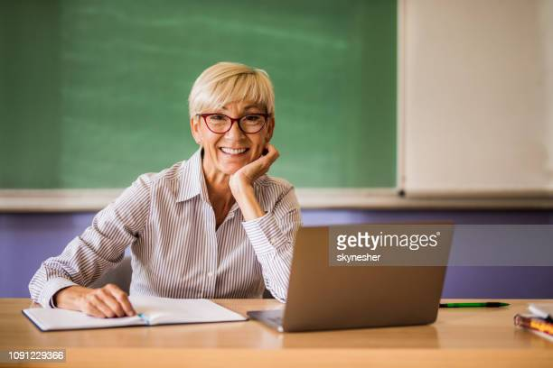happy mature teacher at the desk in the classroom. - instructor stock pictures, royalty-free photos & images