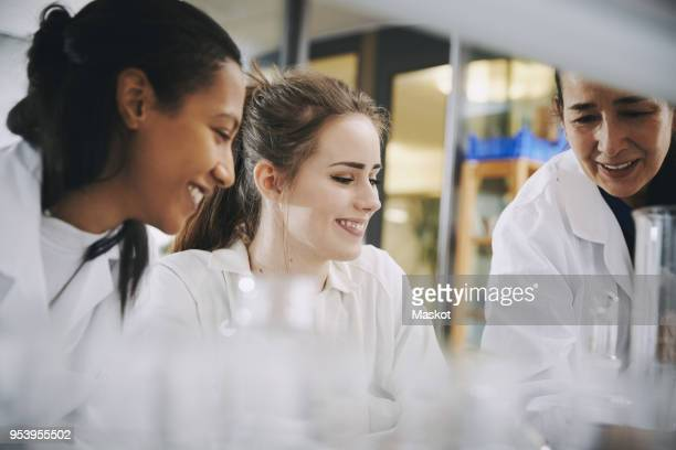 happy mature teacher with young multi-ethnic female students learning at chemistry laboratory - scientificsubjects stock pictures, royalty-free photos & images