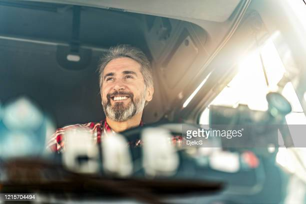 happy mature truck driver driving his truck to a warehouse. - truck driver stock pictures, royalty-free photos & images