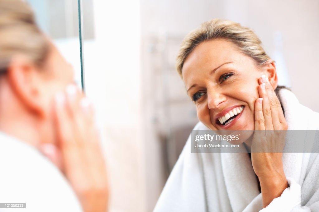Heureux mature femme admirant elle-même dans le miroir : Photo