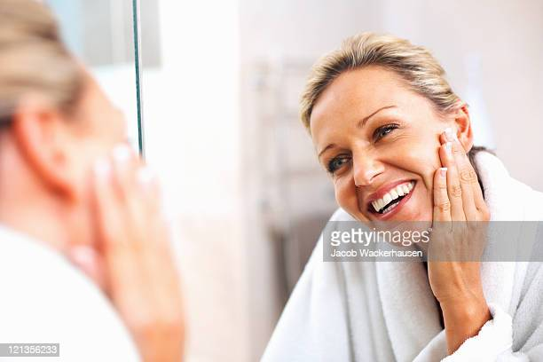 happy mature woman admiring herself in the mirror - beautiful woman stockfoto's en -beelden