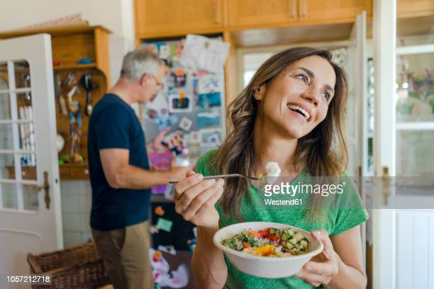 happy mature woman at home eating a salad with man in background - ehefrau stock-fotos und bilder