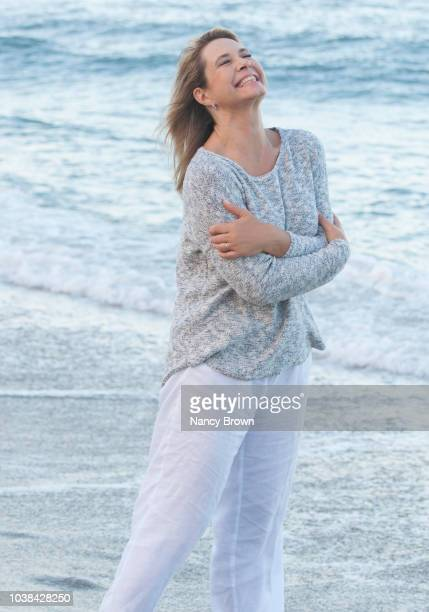 happy mature woman by ocean. - one mature woman only stock pictures, royalty-free photos & images
