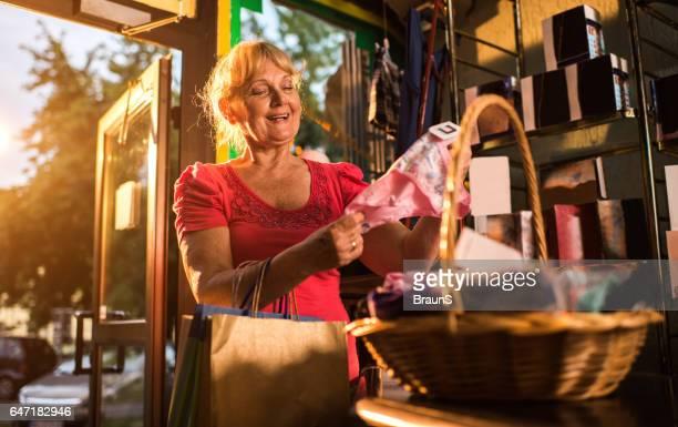 mulher madura feliz escolhendo calcinhas em uma boutique. - calcinha - fotografias e filmes do acervo