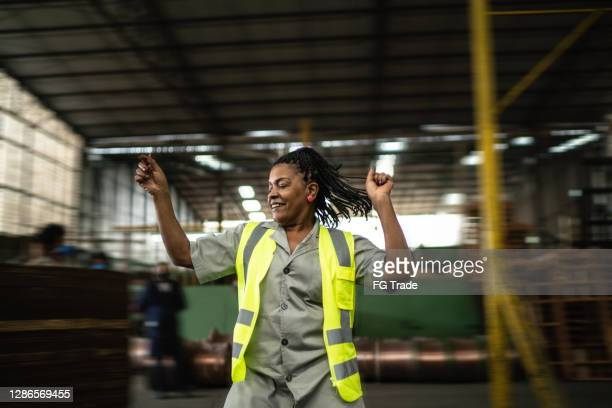 happy mature woman dancing in a industry - carefree stock pictures, royalty-free photos & images