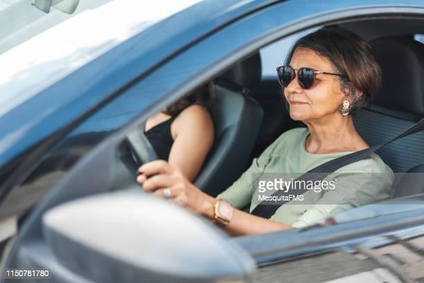 gelukkige rijpe vrouw het besturen van een auto - blauwe riem stockfoto's en -beelden