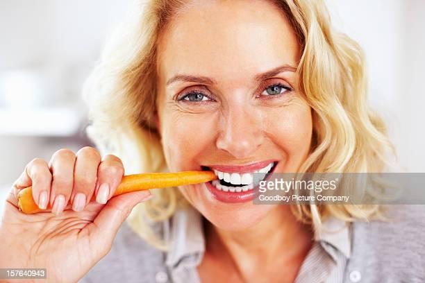 Mujer madura feliz comiendo una zanahoria