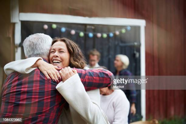 Happy mature woman embracing man while standing at farm