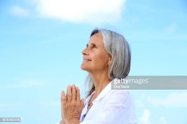 happy mature woman enjoys stretches on beach - só uma mulher idosa imagens e fotografias de stock