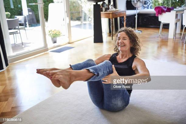 happy mature woman exercising at home - lifestyle stock pictures, royalty-free photos & images